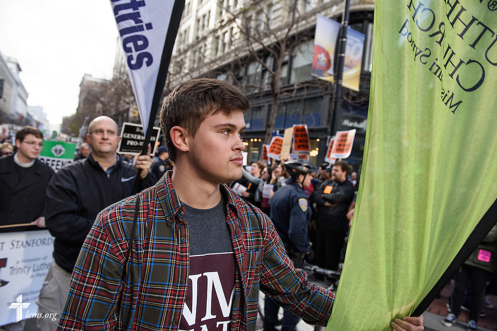 Sterling Zill, son of the Rev. Marcus Zill, director of Campus Ministry and LCMS U in the Office of National Mission, carries the LCMS banner past heckling counter-protestors at the 2016 Walk for Life West Coast on Saturday, Jan. 23, 2016, in San Francisco. LCMS Communications/Erik M. Lunsford