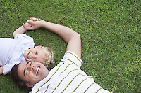 Father and young son (3-4) lying on grass portrait