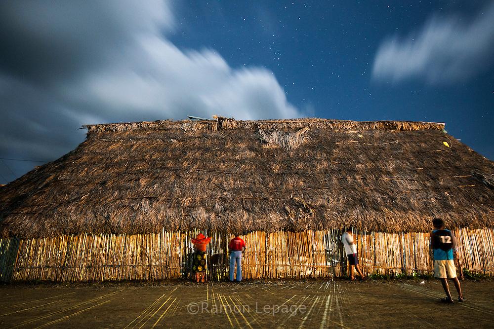 Vista nocturna del exterior de la choza del Congreso indígena Guna de Ustupu.  La  isla de Ustupu, perteneciente a la comarca indígena  Guna Yala,  forma parte del archipiélago de 365 islas a lo largo de la costa caribe noreste de Panamá..En Ustupu se genero la  Revolución Guna  en 1925, en la que los indígenas Gunas se defendieron ante las autoridades panameñas, que obligaban a los indígenas a occidentalizar su cultura a la fuerza. los Gunas con el aval del gobierno panameño, crearon un territorio autónomo llamado comarca indígena de Guna Yala, para garantizar la seguridad de la población y cultura Guna..(Ramón Lepage).