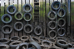 © Licensed to London News Pictures. <br /> 17/03/2015. <br /> <br /> South Gare, Teesside.<br /> <br /> Tyres suspended on the side of a small jetty to cushion the boats that might pull alongside are revealed at low tide in an area known as Paddy's Hole at South Gare on the mouth of the River Tees.<br /> <br /> Photo credit : Ian Forsyth/LNP