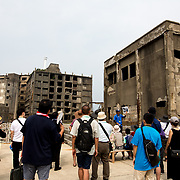 "NAGASAKI, JAPAN - AUGUST 8: Tourists visit a part of Hashima Island, commonly known as Gunkanjima or ""Battleship Island"" in Nagasaki Prefecture, southern Japan on August 8, 2017. The island was a coal mining facility until its closure in 1974 is a symbol of the rapid industrialization of Japan, a reminder of its dark history as a site of forced labor during the Second World War. The island now is recognized as UNESCO's World Heritage sites of Japan's Meiji Industrial Revolution. (Photo: Richard Atrero de Guzman/NURPhoto)"