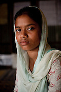 "Child bride Rina Akhter Meghla (14) sits for a portrait in the meeting hut of a Children's Group in Bhashantek Basti (Slum) in Zon H, Dhaka, Bangladesh on 23rd September 2011. ""I was about to be wed. The groom was already selected. I told my parents that I didn't want to get married now because I just will be a servant to my husband. I wanted to be independent."" Her parents had said that they wanted to marry her off because she was watching too much television and not doing well in school, after which she promised to stop watching TV and improve her grades. Her ambition is to be a police inspector. The Bhashantek Basti Childrens Group is run by children for children with the facilitation of PLAN Bangladesh and other partner NGOs. Slum children from ages 8 to 17 run the group within their own communities to protect vulnerable children from child related issues such as child marriage. Photo by Suzanne Lee for The Guardian"