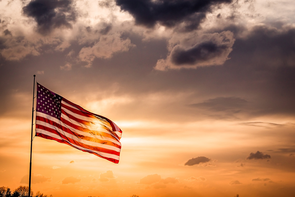 Dramatic sunset featuring the flag of the United States of America.