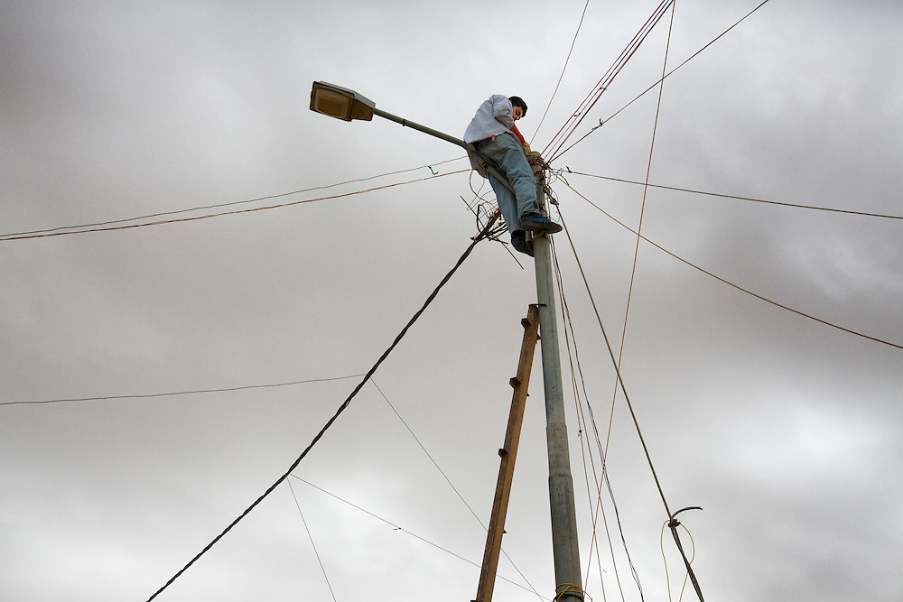 A man has climbed a flagpole and is illegally tapping into the power grid. This is common practice and has resulted in dozens of electrocutions and some deaths within the camp according to residents. Jan. 27, 2014. Zaatari Camp, Jordan. (Photo by Gabriel Romero/Alexia Foundation ©2014)
