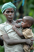 A Pygmy woman feeds a young hungry member of the tribe. Uganda, East Africa.