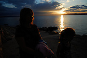 Near silhouette of mother and daughter (5 years old) walking along beach with sun setting over water in background. Makarska, Croatia