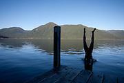 Mark Chambers dives into lake Rotoroa beside sabine hut. Nelson lakes.