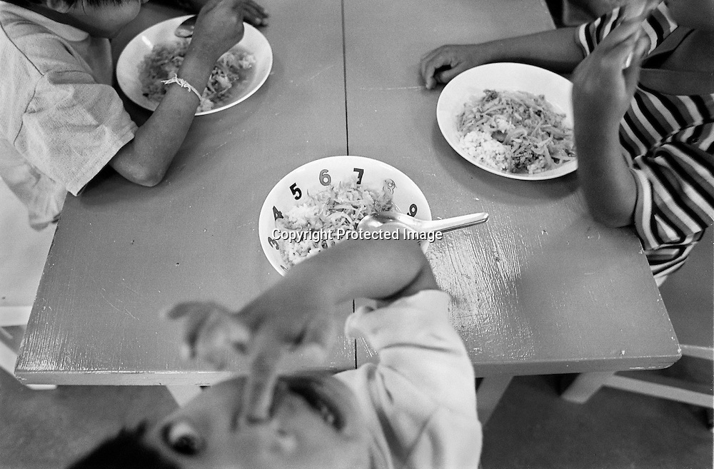 Die Aids-Waise LUKNAAM, 3 Jahre alt beim gemeinsamen Abendessen der Kinder im Kinderstern. .Provinz Lop Buri, Thailand..LUKNAAM, age 3, together with with other childeren during dinnertime, at the commonhouse..Lop Buri, Thailand..