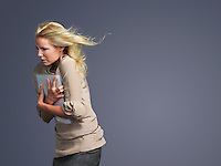 Woman with hair blowing facing into wind side view