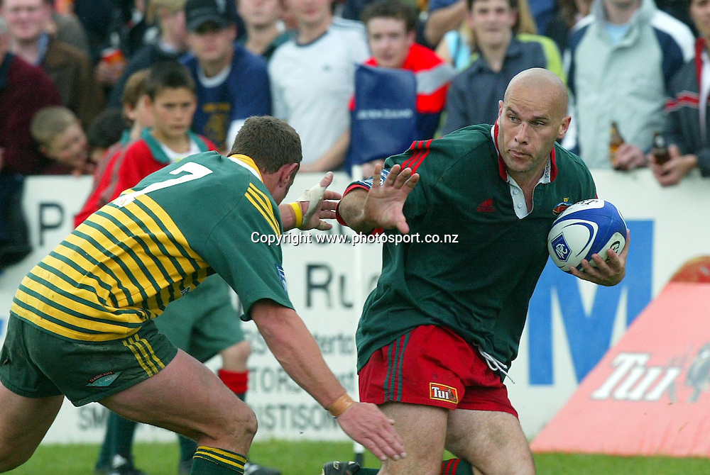 Bush's Nathan Riwai-Couch fends off Mid Canterbury's Andrew Morgan during the NPC Rugby Div 3 Semi final in Masterton, New Zealand. 09 October 2004.<br /> Photo: Marty Melville/Photosport