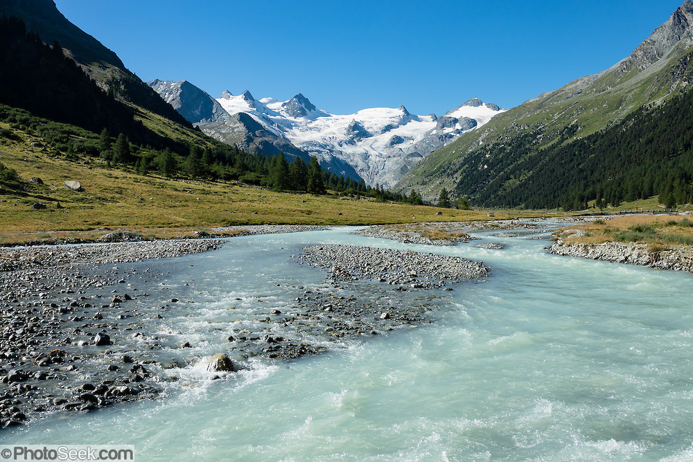 "The icy Bernina Range rises above Ova da Roseg river valley, near Pontresina, Switzerland, in the Bernina Alps, Europe. Roseg Glacier flows from Piz Glüschaint (3594 m/11,791 ft). Val Roseg is in the Swiss canton of Graubünden (or Grisons / Grigioni / Grischun); the lower Roseg Valley is in Pontresina, whereas the upper valley is in an exclave of Samedan Municipality. Hike from Pontresina up Roseg Valley to Fuorcla Surlej for stunning views of Piz Bernina and Piz Roseg, finishing at Corvatsch Mittelstation Murtel cable car. Walking 14 km, we went up 1100 meters and down 150 m. Optionally shorten the hike to an easy 4 km via round trip lift. The Swiss valley of Engadine translates as the ""garden of the En (or Inn) River"" (Engadin in German, Engiadina in Romansh, Engadina in Italian), and is part of the Danube basin."
