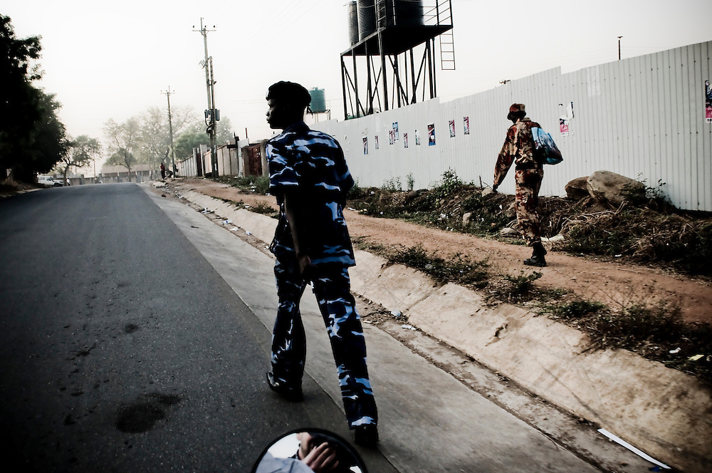 A police officer & SPLA member walk down the morning streets of Juba, Southern Sudan's capital city. Southern Sudan will vote on January 9 to decide whether or not to remain as part of Sudan or set off alone as the world's newest country. (© William B. Plowman)