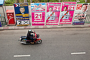 22 JUNE 2011 - BANGKOK, THAILAND: Traffic goes be election posters on Sukhumvit Road in Bangkok Wednesday. Yingluck Shinawatra, leader of the Pheua Thai party is running against  incumbent Prime Minister Abhisit Vejjajiva, head of the Democrat party. Yingluck is the youngest sister of exiled former Prime Minister Thaksin Shinawatra, deposed by a military coup in 2006. Yingluck is currently leading in opinion polls, running well ahead of the Democrat party, which in one form or another has ruled Thailand for most of the last 60 years.   Photo by Jack Kurtz