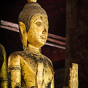 An old gold-leaf Buddha statue at Wat Mai Suwannaphumaham.  Wat Mai, as it is often known, is a Buddhist temple in Luang Prabang, Laos, located near the Royal Palace Museum. It was built in the 18th century and is one of the most richly decorated Wats in Luang Prabang.