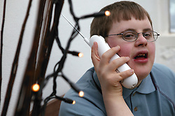 Teenage Downs Syndrome boy using a portable telephone,