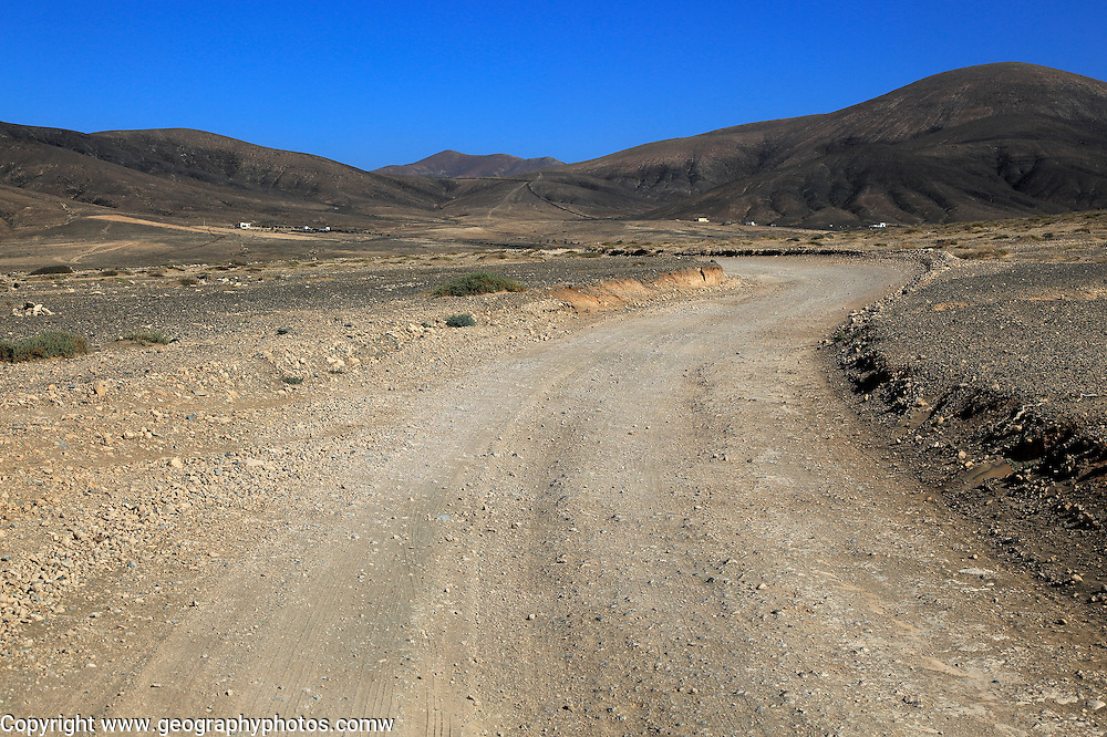 Dirt road crossing dry barren mountain landscape near Paraja, Fuerteventura, Canary Islands, Spain