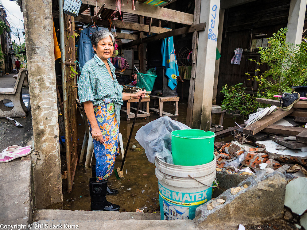 16 NOVEMBER 2015 - BANGKOK, THAILAND:  A woman stands in the doorway of her home in the Wat Kalayanamit neighborhood. She's being evicted from her home and is one of the last people living in the neighborhood. Fifty-four homes around Wat Kalayanamit, a historic Buddhist temple on the Chao Phraya River in the Thonburi section of Bangkok, are being razed and the residents evicted to make way for new development at the temple. The abbot of the temple said he was evicting the residents, who have lived on the temple grounds for generations, because their homes are unsafe and because he wants to improve the temple grounds. The evictions are a part of a Bangkok trend, especially along the Chao Phraya River and BTS light rail lines. Low income people are being evicted from their long time homes to make way for urban renewal.          PHOTO BY JACK KURTZ