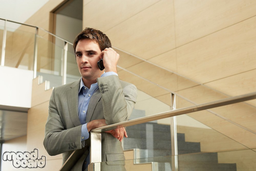 Businessman talking on cell phone standing on stairs