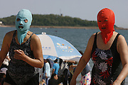 QINGDAO, CHINA - JUNE 02: (CHINA OUT) <br /> <br /> People enjoy themselves with nylon masks at a beach on June 2, 2013 in Qingdao, Shandong Province of China. The mask, which was invented by a woman about seven years ago, is used to block the sun's rays. The mask is under mass production and is on sale at local swimwear stores. <br /> ©ChinaFoto/Exclusivepix