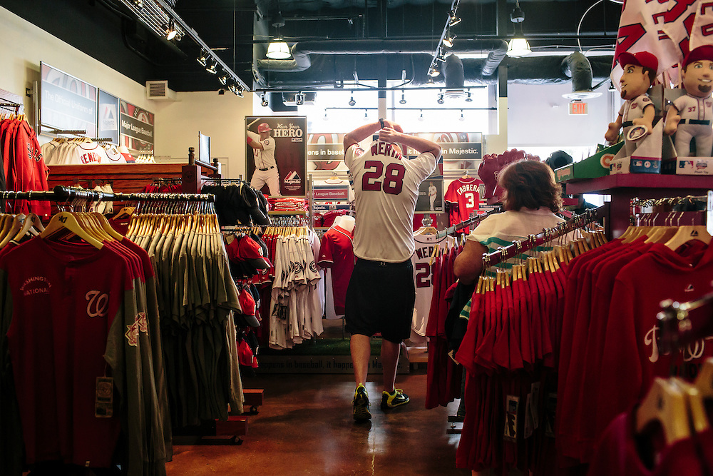 Stephen Riley of Alexandria, Va. tries on a Jason Werth baseball jersey at the Washington Nationals Clubhouse Team Store on Sept. 18, 2014. The Nationals and Baltimore Orioles clinched the first two post season spots within hours of one another.