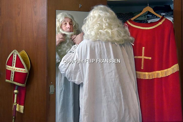 Nederland, Millingen, 15-11-2017Een hulpsint, hulpsinterklaas bereidt zich voor op de intocht. Hij past zich het pak, de mantel, baard en mijter aan. Deze Sint doet het al bijna 50 jaar en houdt er mee op als de Pieten in het dorp niet meer zwart mogen zijn.Foto: Flip Franssen