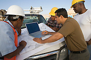 Four construction workers standing in front of car on construction site