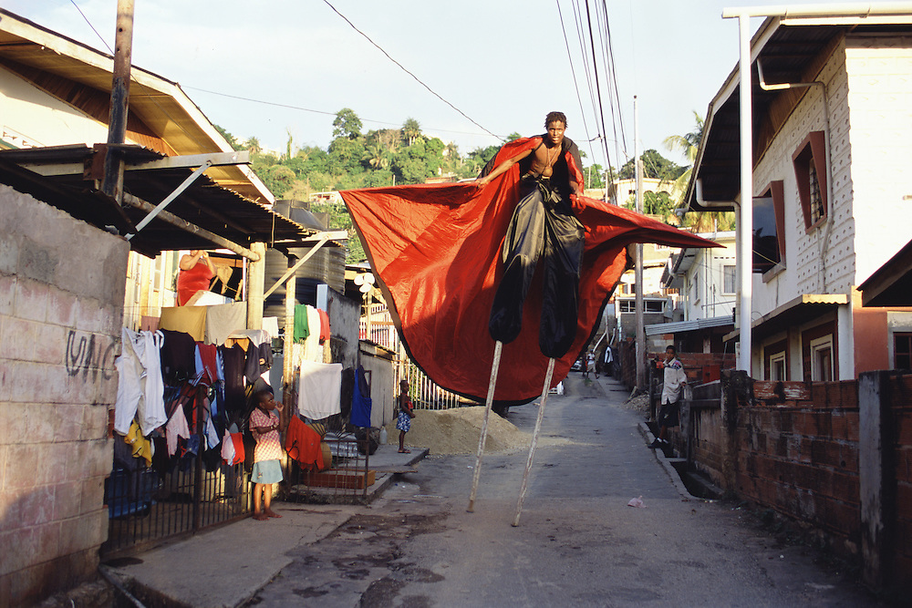 """Trinidad and Tobago """"MOKO JUMBIES: The Dancing Spirits of Trinidad"""". (Rodney Barrow practices the choreography for his portrayal of the Midnight Robber in a back alley in Cocorite. Costume design by Laura Anderson Barbata.).A photo essay about a stilt walking school in Cocorite, Trinidad..Dragon Glen de Souza founded the Keylemanjahro School of Art & Culture in 1986. The main purpose of the school is to keep children off the streets and away from drugs..He first taught dances like the Calypso, African dance and the jig with his former partner Cathy Ann Samuel.  Searching for other activities to engage the children in, he rediscovered the art of stilt-walking, a tradition known in West Africa as the Moko Jumbies , protectors of the villages and participants in religious ceremonies. The art was brought to Trinidad by the slave trade and soon forgotten..Today Dragon's school has over 100 members from age 4 and up..His 2 year old son Mutawakkil is probably the youngest Moko Jumbie ever. The stilts are made by Dragon and his students and can be as high as 12-15 feet. The children show their artistic talents mostly at the annual Carnival, which today is unthinkable without the presence of the Moko Jumbies. A band can have up to 80 children on stilts and they have won many of the prestigious prizes and trophies that are awarded by the National Carnival Commission. Designers like  Peter Minshall , Brian Mac Farlane and Laura Anderson Barbata create dazzling costumes for the school which are admired by thousands of  spectators. Besides stilt-walking the children learn the limbo dance, drumming, fire blowing and how to ride  unicycles..The school is situated in Cocorite, a suburb of Port of Spain, the capital of Trinidad and Tobago..all images © Stefan Falke"""