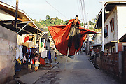 "Trinidad and Tobago ""MOKO JUMBIES: The Dancing Spirits of Trinidad"". (Rodney Barrow practices the choreography for his portrayal of the Midnight Robber in a back alley in Cocorite. Costume design by Laura Anderson Barbata.).A photo essay about a stilt walking school in Cocorite, Trinidad..Dragon Glen de Souza founded the Keylemanjahro School of Art & Culture in 1986. The main purpose of the school is to keep children off the streets and away from drugs..He first taught dances like the Calypso, African dance and the jig with his former partner Cathy Ann Samuel.  Searching for other activities to engage the children in, he rediscovered the art of stilt-walking, a tradition known in West Africa as the Moko Jumbies , protectors of the villages and participants in religious ceremonies. The art was brought to Trinidad by the slave trade and soon forgotten..Today Dragon's school has over 100 members from age 4 and up..His 2 year old son Mutawakkil is probably the youngest Moko Jumbie ever. The stilts are made by Dragon and his students and can be as high as 12-15 feet. The children show their artistic talents mostly at the annual Carnival, which today is unthinkable without the presence of the Moko Jumbies. A band can have up to 80 children on stilts and they have won many of the prestigious prizes and trophies that are awarded by the National Carnival Commission. Designers like  Peter Minshall , Brian Mac Farlane and Laura Anderson Barbata create dazzling costumes for the school which are admired by thousands of  spectators. Besides stilt-walking the children learn the limbo dance, drumming, fire blowing and how to ride  unicycles..The school is situated in Cocorite, a suburb of Port of Spain, the capital of Trinidad and Tobago..all images © Stefan Falke"
