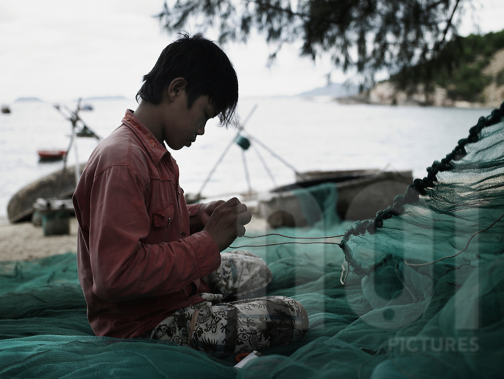 A young vietnamese boy repairs fishing net along a Bai Xep's beach, Quy Nhon area, Vietnam, Asia.