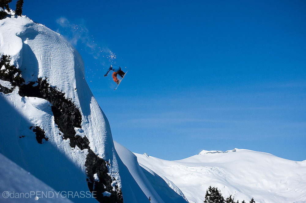 Professional snowboarder Benji Ritchie sails through the blue skies of BC. The mountains around Whistler, British Columbia are a hotbed for snowboard action.