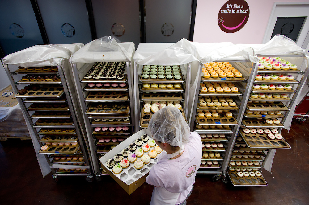 """""""It's like a smile in a box"""", is the sign in the background, as employee Chelsey Demas fills orders by putting cupcakes in boxes inside the bakery. Icing on the Cupcake recently opened a huge bakery and kitchen in West Rocklin, it's the fourth location for the local business, which is enjoying marked success despite a surplus of cupcakeries and economic doldrums. August 12, 2011."""