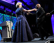 """Former U.S. Secretary of State Hillary Rodham Clinton welcomes Archbishop Desmond Tutu, who was honored at the Starkey Hearing Foundation's """"So the World May Hear"""" Awards Gala on Sunday, July 20, 2014 in St. Paul, Minn. The foundation is a member of the Clinton Global Initiative and gives away more than 100,000 hearing aids in the U.S. and around the world annually. (Photo by Diane Bondareff/Invision for Starkey Hearing Foundation/AP Images)"""