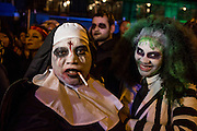 New York, NY - 31 October 2015. A parade-goer dressed as a nun, made up to look like a cross has been incised on her forehead, and smoking a cigarette, in the annual Greenwich Village Halloween Parade