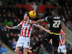 Cheltenham Town's Denny Johnstone and Bury's Nathan Cameron challenge for possession in mid-air.  - Photo mandatory by-line: Nizaam Jones - Mobile: 07966 386802 - 14/02/2015 - SPORT - Football - Cheltenham - Whaddon Road - Cheltenham Town v Bury - Sky Bet League Two
