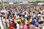 13 MAY 2013 - BANGKOK, THAILAND: Thousands crowd into the ploughed ground to collect blessed rice seeds at the Royal Ploughing Ceremony. After the ceremony, thousands of Thais, mostly family formers, rush onto the ploughed ground to gather up the blessed rice seeds sown by the Brahmin priests. The Royal Plowing Ceremony is held Thailand to mark the traditional beginning of the rice-growing season. The date is usually in May, but is determined by court astrologers and varies year to year. During the ceremony, two sacred oxen are hitched to a wooden plough and plough a small field on Sanam Luang (across from the Grand Palace), while rice seed is sown by court Brahmins. After the ploughing, the oxen are offered plates of food, including rice, corn, green beans, sesame, fresh-cut grass, water and rice whisky. Depending on what the oxen eat, court astrologers and Brahmins make a prediction on whether the coming growing season will be bountiful or not. The ceremony is rooted in Brahman belief, and is held to ensure a good harvest. A similar ceremony is held in Cambodia.    PHOTO BY JACK KURTZ