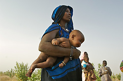 A mother gives her child some water during a break while she works  in a garden that Oxfam supported in the village of Intedeyne March 14, 2007. In this arid landscape, it requires a lot of work to maintain any kind of agriculture but it is one of the projects along with  education that Oxfam is supporting here.  Mali has the highest percentage of people living below the poverty line in any country in the world. Ninety percent of Malians survive on less than two dollars a day. In 2000, following the international commitments on education, the Government of Mali created a ten year education development program and as a result, donars provided two and a half times more aid to basic education. As a result, more than 6 out of 10 primary school age children are now enrolled in Mali. Yet the challenge to educate still exists and particularly for girls. Female literacy rates never reach even 50 percent of male literacy rates.Eight of the world's ten countries farthest from the gender parity goal are in West Africa: Niger, Chad, Burkina Faso, Mali, Ivory Coast, Guinea-Bissau, Benin and Guinea.