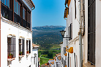 The view to the rolling hills of Southern Spain is framed between attached homes built onto the steeply terraced terrain.