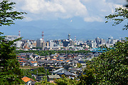 Photo shows the  view over the city from the Toyama Folk Village in Toyama City Japan. Forming a backdrop to the city are the Tateyama mountains.