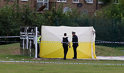 © Licensed to London News Pictures. 18/08/2011. Police stand over a forensics tent in Ponders End Recreation Ground in Enfield, London today (18/08/2011) where a 14 Year-old boy was found stabbed to death yesterday afternoon. Photo credit: Ben Cawthra/LNP