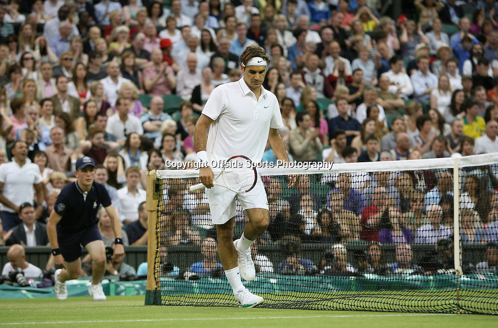 29/06/2012 - Wimbledon (Day 5) - Roger FEDERER (SUI) vs. Julien BENNETEAU (FRA) - Roger Federer looks dejected as he gets his feet tangled up the net - Photo: Simon Stacpoole / Offside.