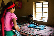 Nisha Darlami, 19, prepares to lay her 1 month old baby girl, Bushpa, on the bed in her mother's house in Kalyan Village, Surkhet district, Western Nepal, on 30th June 2012. Nisha eloped with her step nephew when she was 13 but the couple used contraceptives for the next 6 years to delay pregnancy until she turned 18. In Surkhet, StC partners with Safer Society, a local NGO which advocates for child rights and against child marriage. Photo by Suzanne Lee for Save The Children UK