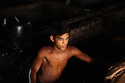 A boy is taking a break while working inside a bath during the process of liming, the removal of hair and impurities with the use of water and various agents, in an illegal tannery unit inside Jajmau, Kanpur, Uttar Pradesh. Children are largely employed to work on scraps, or little pieces of skin, like the head and the ears of the animal, which will become a small bag, a wallet, or maybe a cheap phone leather case.
