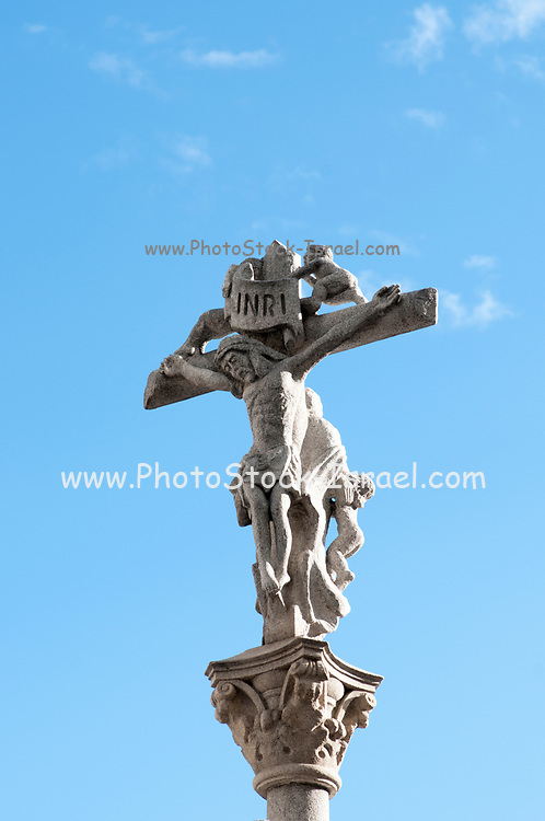 A crucifix with the inscription INRI (Jesus the Nazarene, King of the Jews) on blue sky background
