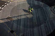 A cyclist passes over a mini-roundabout in a City of London side street.