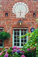 A hotel sign on a typical red brick building in Collonges-la-Rouge, Dordogne, France