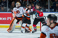 KELOWNA, CANADA - NOVEMBER 25: Kyle Topping #24 of the Kelowna Rockets is checked by David Quenneville #19 in front of the net of Michael Bullion #30 of the Medicine Hat Tigers during second period on November 25, 2017 at Prospera Place in Kelowna, British Columbia, Canada.  (Photo by Marissa Baecker/Shoot the Breeze)  *** Local Caption ***