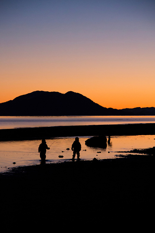 Two children walk along the beach in Gustavus, Lemesuire Island in the background during a warm sunset.