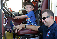 Brayden Cohen (left) 2, of Yardley, Pennsylvania sits in the drivers seat of a Newtown fire truck as Ryan Williams of the Newtown Fire Company shares a laugh during the annual first Fourth event at Newtown Middle School Saturday July 11, 2015 in Newtown, Pennsylvania. The celebration was held a week late this year cause fireworks company couldn't make it on July 4th. (Photo by William Thomas Cain)