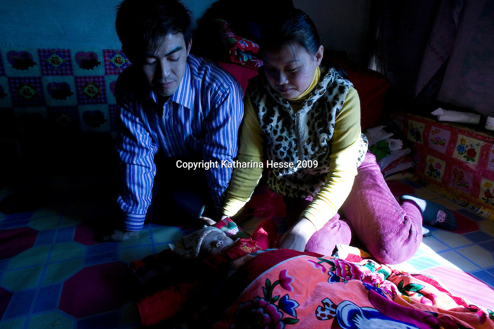NORTHERN HEBEI PROVINCE, JANUARY 26, 2009:<br /> Mr Lu, a textile worker in Beijing, his wife look on their newborn baby in Lu's parents house.<br />  <br /> Lu went to Beijing 8 years ago as he couldn't find a job in China's countryside.<br /> He was employed in a textile factory that went banctrupt last October. Lu and his 63 colleagues were still owed payment for 4 months, but their boss refused to pay them. They didn't know the law, nor did any of them have a contract.  <br /> At the end of January, Lu and his co-workers went to see the bosses' mother to negociate, then the union and in the end the government. They were threatened with jail . At the end of the day , a man from the union came by ( on behalf of the government )and all but an underaged worker received their due salaries.<br /> Now Lu is unemployed like 20 milion other migrant workers in China who have been laid off as a result of the financial crisis.<br /> <br /> <br /> China's Communist Party  which will celebrate its 60th anniversary in October, currently faces its biggest challenge since the beginning of the economic reforms 30 years ago  : &quot; The phase of  rapid economic growth is over. For the first time the government is threatened with a  mistrust of a wide section of the population&quot;, warns the Communist party's Shang Dewen in Beijing.   <br /> Not only the China's poorest worry about the furture, but as well China's middle class is concerned about the crisis.     1,5 Millionen university graduates didn't find a job until the end of 2008  and this summer there'll be an additional  6,1 Million new graduates. More than 12 percent of university graduates face unemployment in 2009.