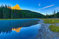 Aplenglow on the mountain peaks surrounding Upper Waterfowl Lake at Sunrise with the mountains reflected the glassy calm waters of the lake.<br /> <br /> &copy;2015, Sean Phillips<br /> http://www.RiverwoodPhotography.com